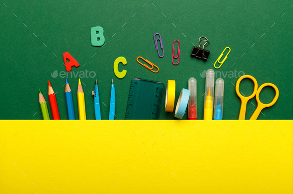 Colorful stationary school supplies on green background - Stock Photo - Images