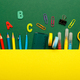 Colorful stationary school supplies on green background - PhotoDune Item for Sale
