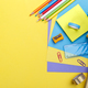 Colorful stationary school supplies on yellow background - PhotoDune Item for Sale