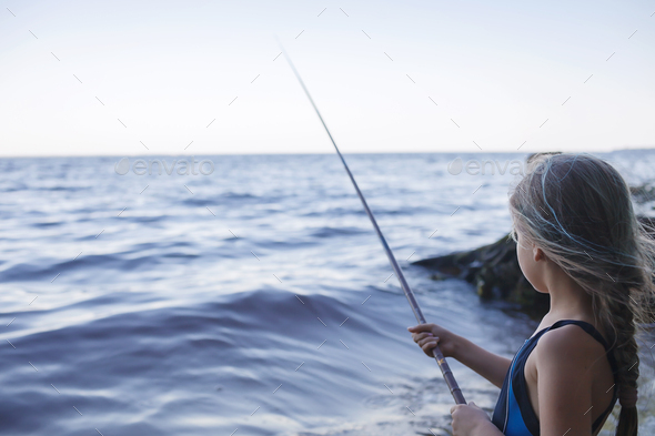 Girl in swimming wear fishing from sea beach in early morning, blue hours, active weekend, camping - Stock Photo - Images