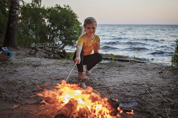 Girl roasting marshmallow to make smores over fire flame during camping, traditional travel food - Stock Photo - Images