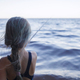 Girl in swimming wear fishing from sea beach in early morning, blue hours, active weekend, camping - PhotoDune Item for Sale