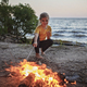 Girl roasting marshmallow to make smores over fire flame during camping, traditional travel food - PhotoDune Item for Sale