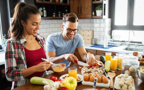 Happy young couple have fun in modern kitchen while preparing fresh food - Stock Photo - Images