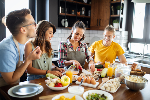 Young group of friends preparing vegetable meal and making fun - Stock Photo - Images