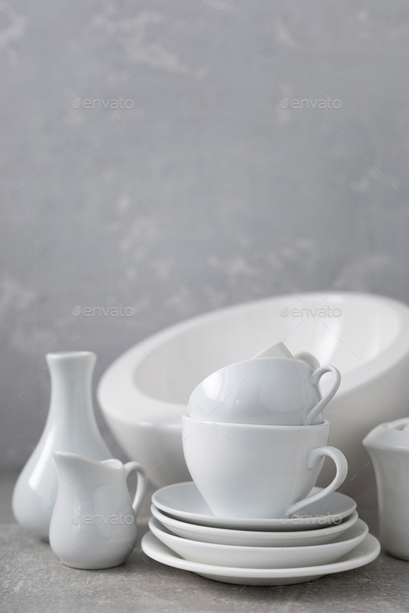 Empty crockery set or ceramic dishes. White kitchen dishware and tableware on table near grey wall - Stock Photo - Images