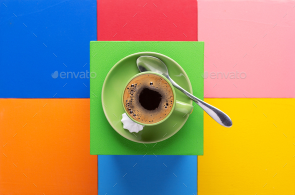 Cup of coffee and spoon at colorful abstract background - Stock Photo - Images