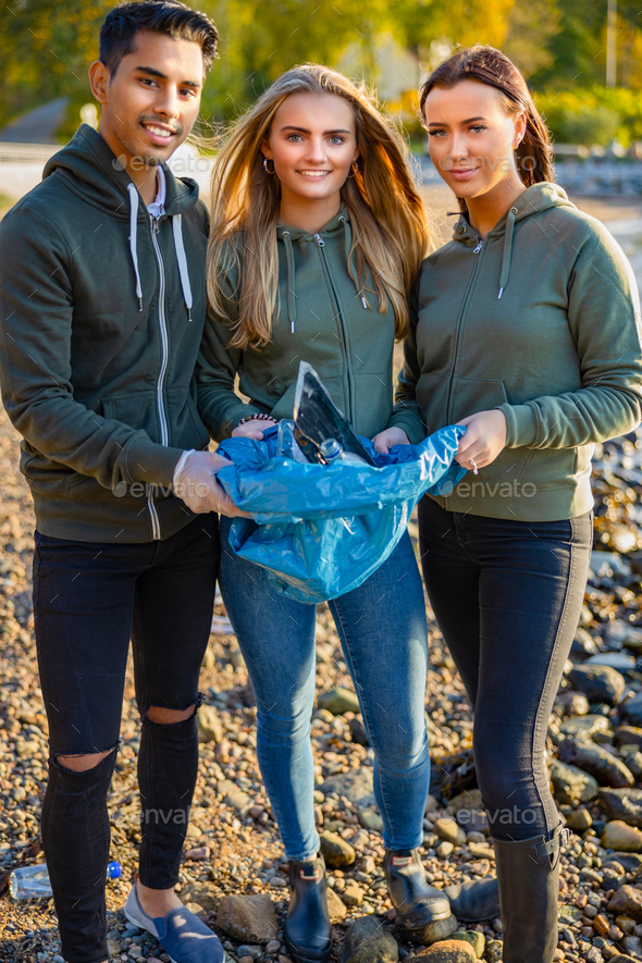 Smiling team of volunteers holding garbage bag at beach - Stock Photo - Images