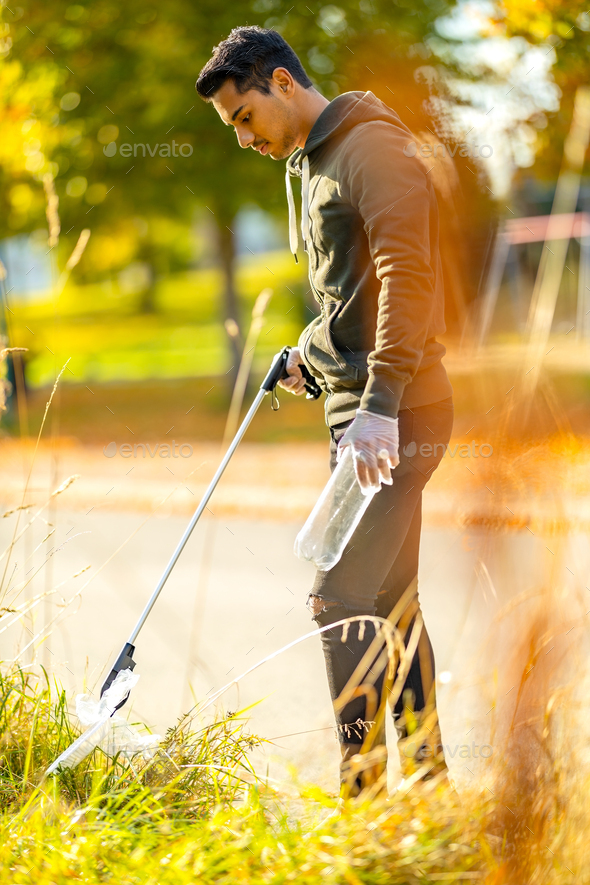 Focused volunteer conserving environment from pollution and plastic - Stock Photo - Images