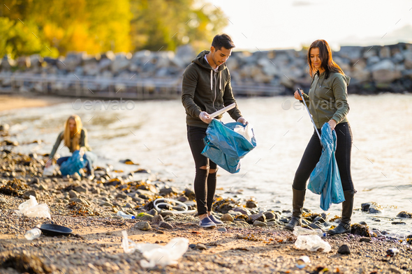 Team of young dedicated volunteers cleaning beach on sunny day - Stock Photo - Images