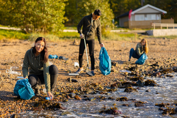 Young woman in a team picking up plastic garbage in bag at beach - Stock Photo - Images