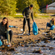 Young woman in a team picking up plastic garbage in bag at beach - PhotoDune Item for Sale