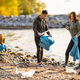 Team of young dedicated volunteers cleaning beach on sunny day - PhotoDune Item for Sale