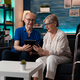 Old adult couple holding digital tablet at home on couch - PhotoDune Item for Sale