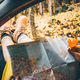 Woman legs stuck out of window reads map sits in automobile - PhotoDune Item for Sale
