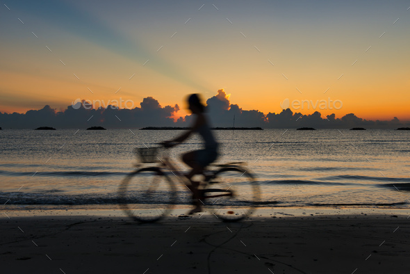 Woman by bicycle at the beach at dawn - Stock Photo - Images
