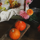 Beautiful pumpkins on wooden bench, colorful dahlias and leaves on cozy rustic chair in room - PhotoDune Item for Sale