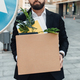 Unemployed businessman standing with box of stuff outdoors, near road sign, lost his job, crop - PhotoDune Item for Sale