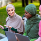 Muslim Woman Showing Smartphone To Friends Recommending Application Outdoors - PhotoDune Item for Sale
