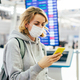 Woman  in a medical mask with a mobile phone at the airport near the electronic board of departure. - PhotoDune Item for Sale