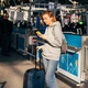 A young woman stands at the airport with a mobile phone and luggage and waits for check-in. - PhotoDune Item for Sale