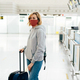A woman passenger in a face shield with luggage in an empty gate of the airport. - PhotoDune Item for Sale