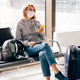 Woman passenger in a medical mask sitting in a chair with a phone waiting at the airport. - PhotoDune Item for Sale