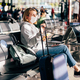 A female passenger in a medical mask is waiting for a flight at the airport. - PhotoDune Item for Sale