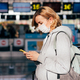 Woman traveler in medical mask with mobile phone at the airport. - PhotoDune Item for Sale