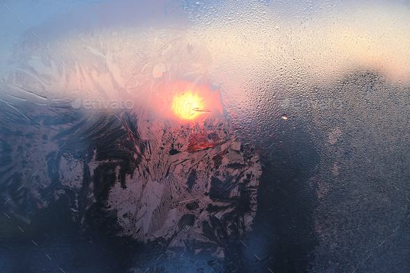Ice pattern and water drops on glass on a sunny winter morning - Stock Photo - Images