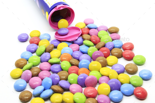 Multicolored glazed chocolate candies out of the container - Stock Photo - Images