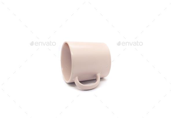 Empty light pink ceramic mug lying on its side - Stock Photo - Images