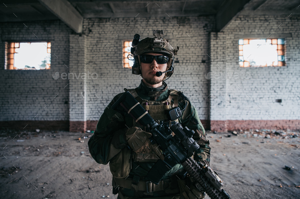Close-up of a professional fully equipped soldier looking at camera - Stock Photo - Images