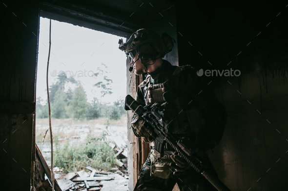 Military man with assault rifle standing inside building, he is ready for combat - Stock Photo - Images