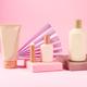 Geometric podium displaying set of body care generic bottles, tubes on pink background. - PhotoDune Item for Sale