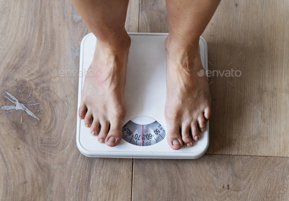 Pregnant woman weighing herself - Stock Photo - Images