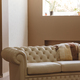 Vintage style beige quilted sofa in modern interior of living room - PhotoDune Item for Sale