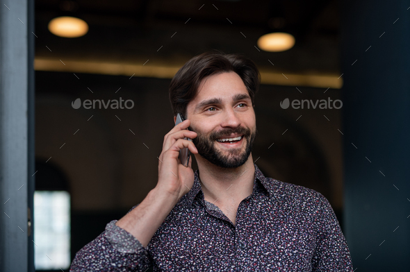 Portrait of young businessman standing indoors, using smarpthone - Stock Photo - Images