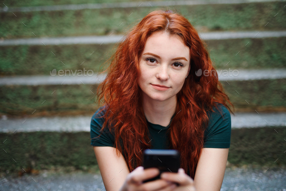 Portrait of young woman with smartphone outdoors in city street, looking at camera - Stock Photo - Images