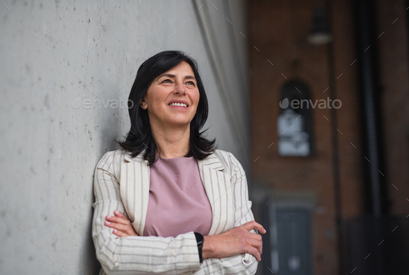 Portrait of senior businesswoman standing indoors in office - Stock Photo - Images