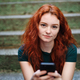 Portrait of young woman with smartphone outdoors in city street, looking at camera - PhotoDune Item for Sale