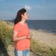 Woman enjoys sea breeze on shore - PhotoDune Item for Sale