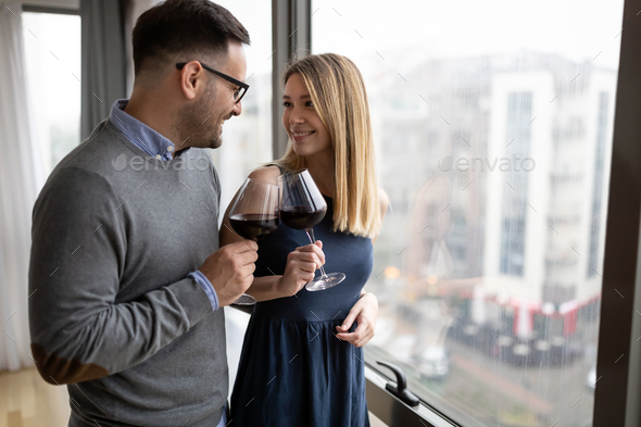 Cheerful happy couple in love drinking wine and having romantic date - Stock Photo - Images