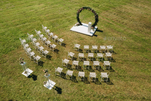 Wedding ceremony on the street on a green lawn with white chairs - Stock Photo - Images
