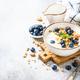 Yogurt granola with fresh blueberries on stone table - PhotoDune Item for Sale