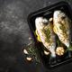 Raw fish dorado in baking sheet at black stone table - PhotoDune Item for Sale