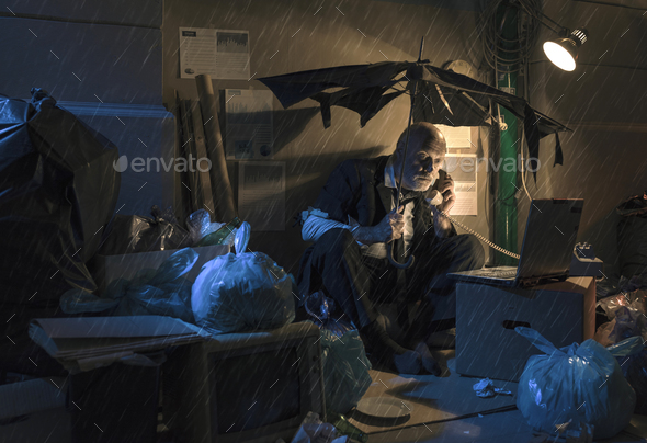 Broke jobless businessman sitting on the street under the rain - Stock Photo - Images