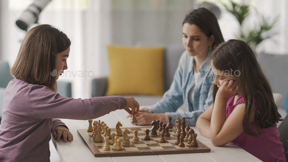Girls playing chess together at home - Stock Photo - Images