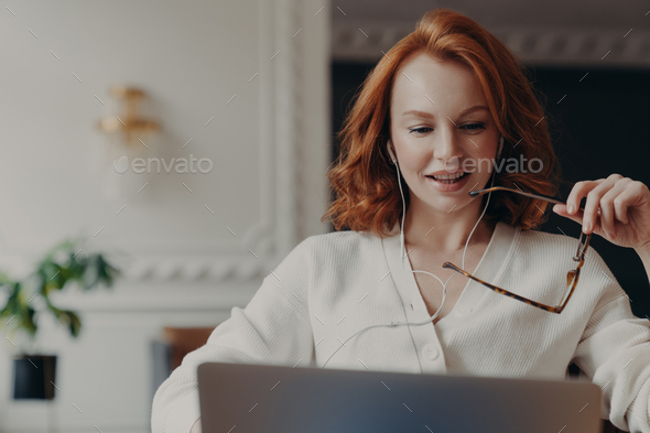 Pleased redhead woman student watches training webinar, - Stock Photo - Images