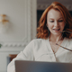 Pleased redhead woman student watches training webinar,